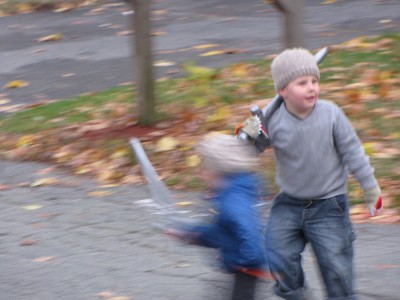 Zion and Harvey running in the street with their swords