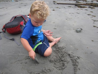 swmsuited Lijah playing in the sand