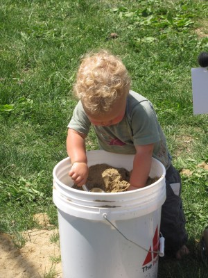 Lijah digging in a five-gallon bucket of sand