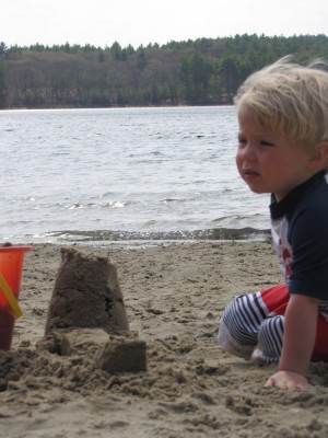 Zion sitting next to his sand castle
