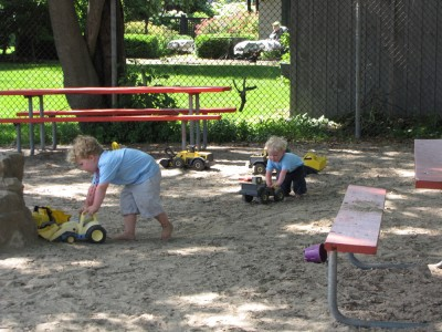 Harvey and Zion pushing sand toys at the Emerson Park playground