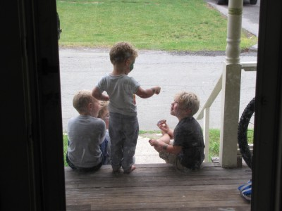 the boys and Nicholas sitting together on the front steps