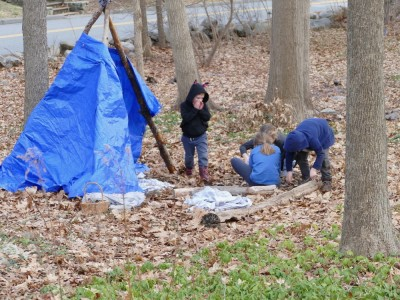 the kids working on a fire by a tarp shelter