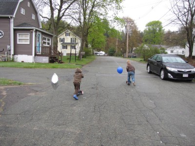 Zion and Harvey scootering down the street with balloons streaming out behind