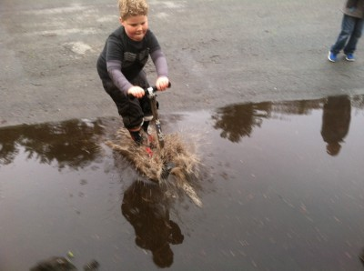 Harvey riding his scooter into a giant puddle