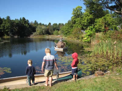 the boys looking at a teapot sculpture alfoat on a pond