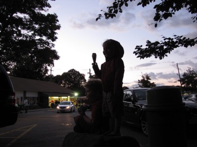 Zion and Harvey silhouetted against the evening sky at the ice cream store