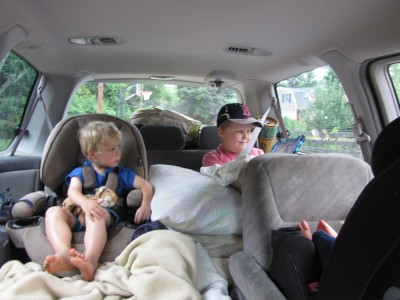 the boys in the car, watching a show before we even leave our street