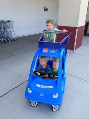 Harvey pushing his brothers in a shopping cart car