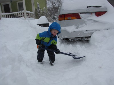 Zion shoveling in the driveway with the snow-covered car behind him