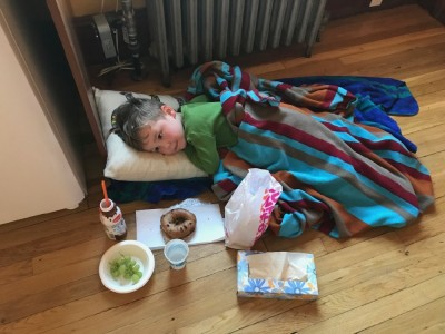 Lijah wrapped in a blanket surrounded by food lying on the church kitchen floor