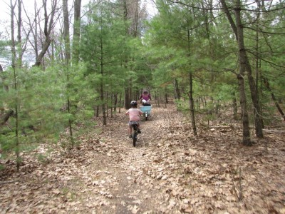 Harvey and Mama (carrying Zion and Lijah) riding on a path through the woods