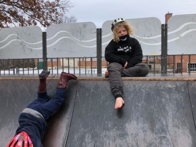 Harvey sitting on the edge of a halfpipe, Lijah sliding down head-first