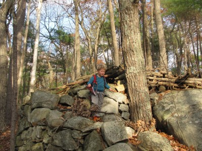 Harvey atop a pile of rocks in the woods, with backpack and sketchbook