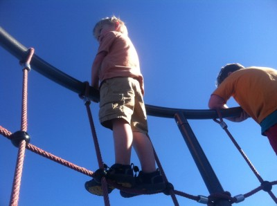 Zion (in shorts) at the top of a climbing structure against the blue sky