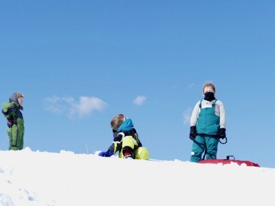 the boys standing against the horizon on the sledding hill