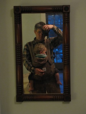 a picture of me in the mirror, with Lijah sleeping in the front-pack