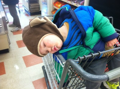 Lijah in monkey hat sleeping slumped over in the grocery store cart