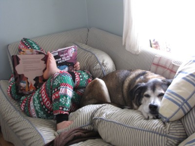 Harvey in PJs reading on the couch, Rascal cuddled on his feet