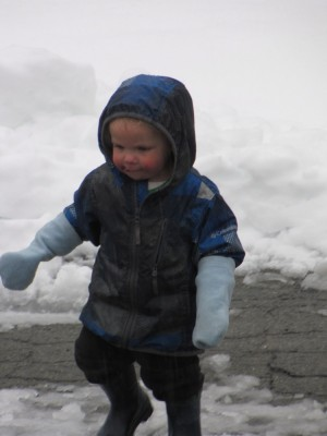 zion playing in the snowy street wearing raincoat and mittens