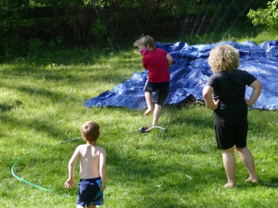 the boys playing with the sprinkler and tarp slip-and-slide