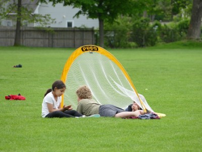 Harvey and Zion lying down with a friend in a soccer goal