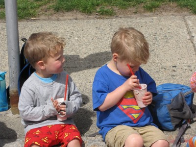 Lijah and Zion sitting on the curb enjoying slushes