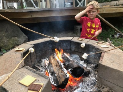 Lijah grimacing at the smoke while toasting a marshmallow