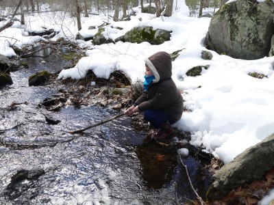 Lijah on the snowy bank holding a stick over a brook