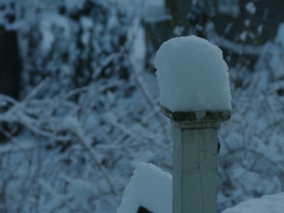 a tall cap of snow on a porch post