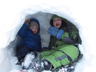 Zion and Harvey smiling in a snow cave