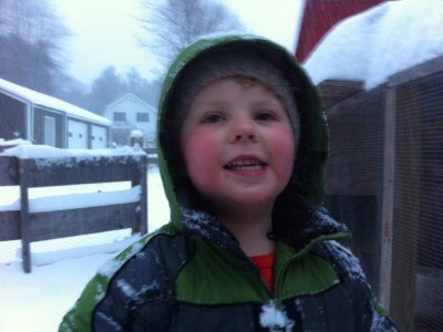 Harvey, snowsuited hooded, smiles for the phone camera next to the chicken coop