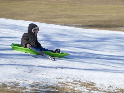 Lijah sledding down a narrow band of snow on a grassy hill