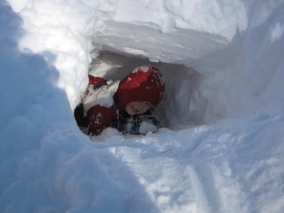 Harvey climbing up through a hole in the snowbank