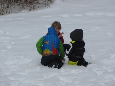 Harvey, Zion, and Eliot kneeling in the snow, deep in coversation
