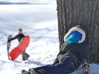 sledding: Lijah resting by a tree, Harvey coming up the hill behind him