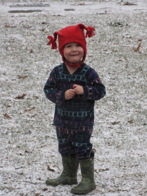 Lijah in PJs, hat, and boots, on the snowy lawn