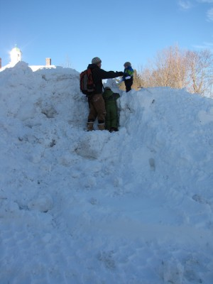 Dan, Harvey, and Zion climbing a giant mountain of snow