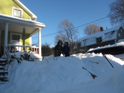 Zion and Harvey atop a giant pile of snow in front of our porch