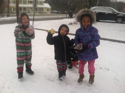 Harvey, Zion, and Nisia in the snow in their PJs