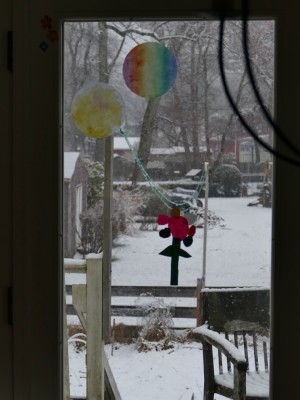 snow falling outside out flower-decorated window