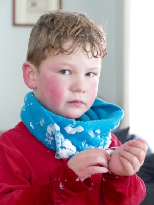 red-cheeked Elijah clearing snow from his shirt cuffs in the living room