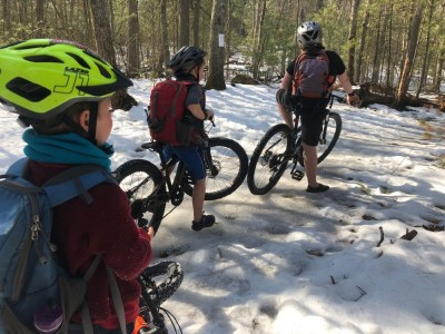 the boys pausing on their bikes on a snowy trail