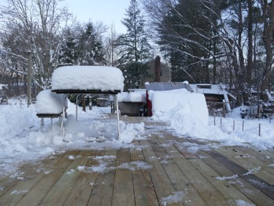 the deck cleared of snow, with snow still piled high on the picnic table