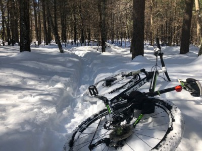 my bike lying in the snow besides a narrow snowy singletrack