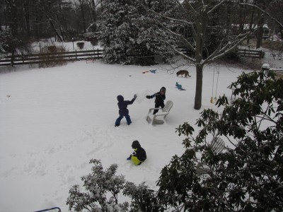 kids having a snowball fight in the snowy yard