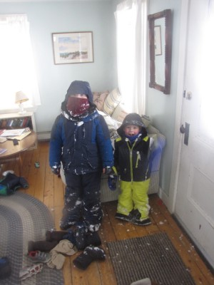 Harvey and Zion just inside the front door, still geared up and covered with snow