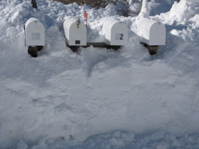 the mailboxes for our street peeking out of the side of a snowbank