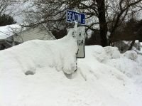 our street sign nearly buried in snow