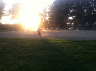 Lijah running across the dusty softball field at sunset